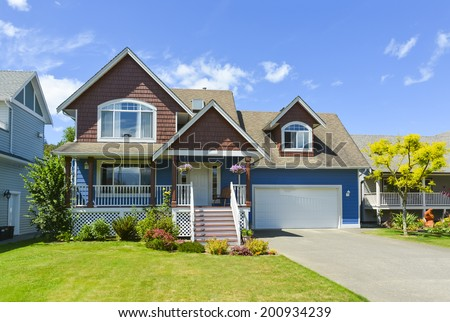 Blue residential house with concrete driveway in front and blue sky background.
