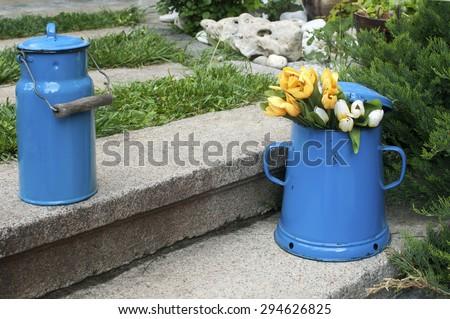 Blue retro metal enamel jugs on old stone steps in back yard house garden