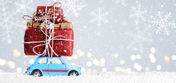 Blue retro toy car delivering Christmas or New Year gifts on festive gray background