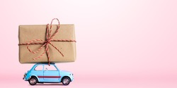 Blue retro toy car delivering gift box for Valentine's day on pink background