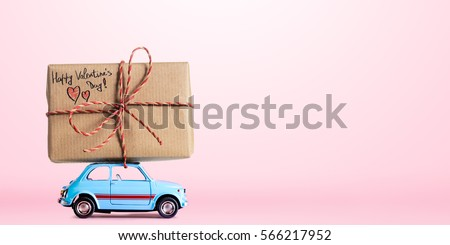Blue retro toy car delivering gift box for Valentine's day on pink background #566217952