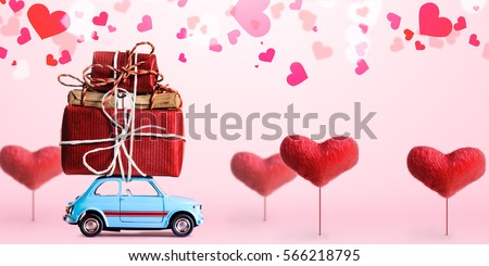 Blue retro toy car delivering gift box for Valentine's day on pink background with heart trees