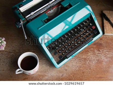 blue retro typewriter sitting on wooden coffee table and cup of coffee, and notepad are good for authors, writers, editors or journalists
