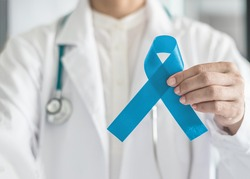 Blue ribbon for prostate cancer awareness campaign and men's health care concept with symbolic bow in doctor's hand