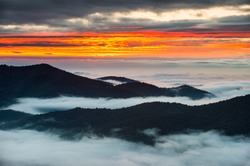 Blue Ridge Parkway North Carolina sunrise scenic mountain landscape photography of sunrise over a fog filled valley in the Appalachian Mountains of the bright orange morning sky near Asheville NC