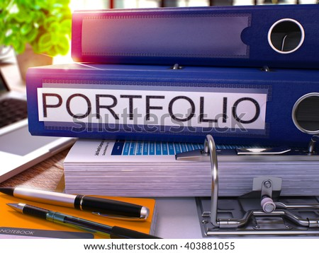 Blue Ring Binder with Inscription Portfolio on Background of Working Table with Office Supplies and Laptop. Portfolio Business Concept on Blurred Background. 3D Render.