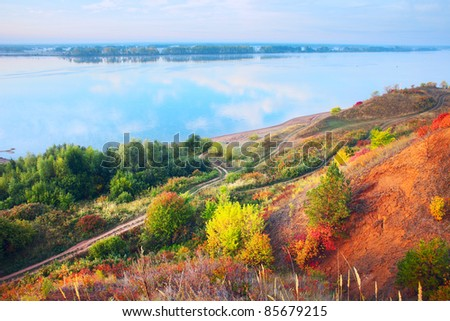 Blue river's coast with autumn trees and roads. Kama river (Ural region). Russia - stock photo