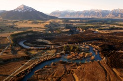 Blue river Upper Clutha with orange trees around and orange country side, Otago New Zealand. Hill Mount Maude on left side. Autumn, sunny, sunset time. Time for flying and see the beauty around
