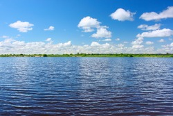 Blue river with ripples and sky with clouds
