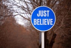 Blue Roadside Sign with the Inscription JUST BELIEVE in the City Park. The Concept Of Motivation.