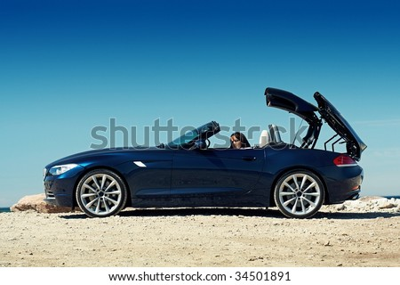 Blue roadster on a sunny day with a folding roof and a girl sitting in the car - stock photo