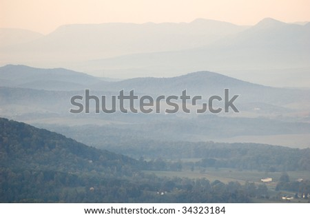 blue rolling hills at sunrise with fog