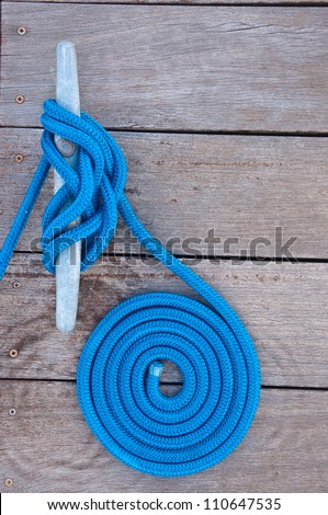Blue rope coiled on a wooden dock and tied to a metal dock cleat.  Cleats are used for securing docks and lines from boats