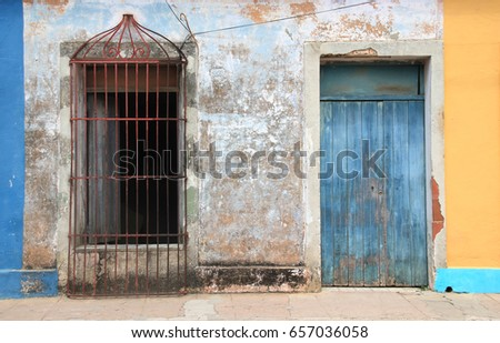 Blue rotten door and rusty Window Grille in colorful Facade in Trinidad, Cuba