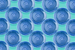 Blue round ceramic plate with spiral pattern, saturated background