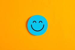 Blue round circle with a happy face icon against yellow background. Positive expression or customer satisfaction in business concept.