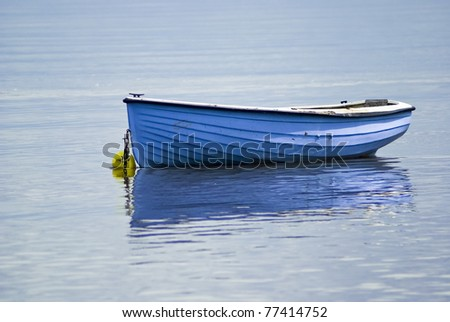 Blue Rowing Boat anchored near Carsthorn (UK OS Ref.NX 994 597) at high tide on a flat calm sunny day July 2007