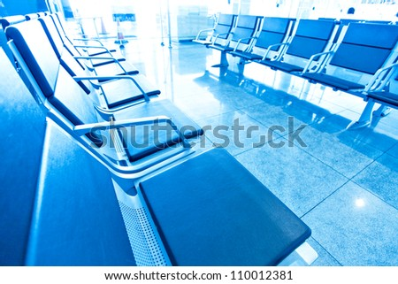 Blue rows of chairs at an empty airport terminal