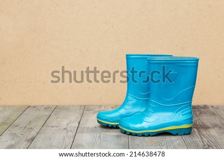 Blue rubber boots on a wooden floor. Autumn season concept