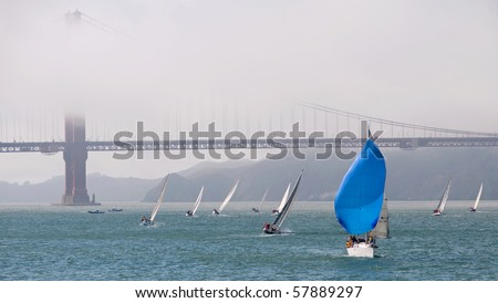 blue sailboat at the golden gate bridge - stock photo
