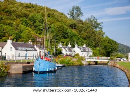 Blue sailboat moored near Bellanoch Swing Bridge at Crinan Canal connecting Crinan with Ardrishaig in Kintyre peninsula, Argyll and Bute, Scotland, UK