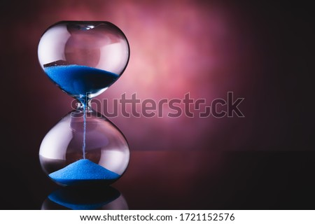 Photo of  Blue sand hourglass on old background