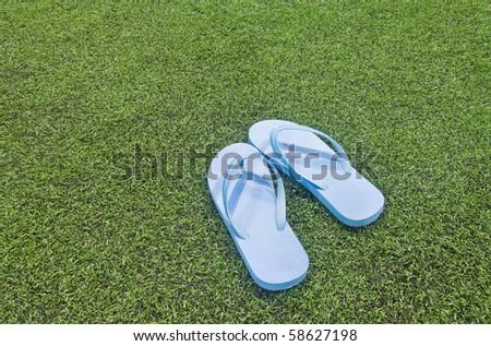 blue sandals/flip flops on the grass