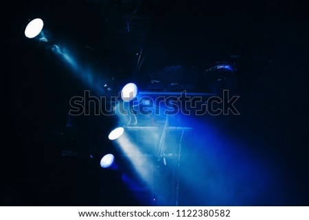 Blue scenic spot lights, beams and smoke over dark background, modern stage illumination #1122380582