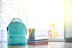 Blue school backpack with school supplies on table over children room interior in sunny day. Back to school concept.