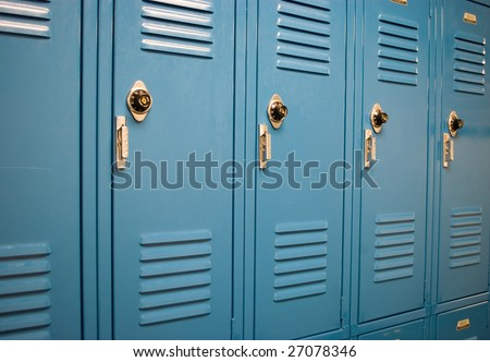 Blue school lockers in a hallway with locks from an angle
