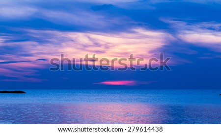 Blue sea and calmly wave at sunrise, a little tidal. Sun just come up. Glittering reflection from sunlight on sea surface.