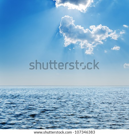 blue sea and cloudy sky with sun over it