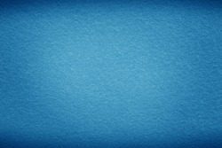 Blue sea background texture with dark vignette. Blue felt fabric background with copy space for design.