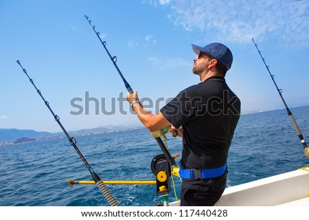 blue sea fisherman in trolling boat in action with downrigger and rod #117440428