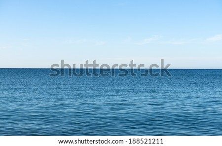 Blue sea horizon line, with blue sky and withe clouds.