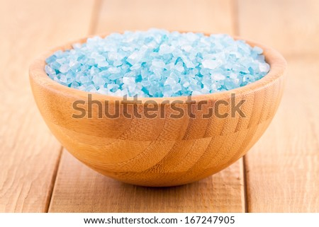 blue Sea salt crystals in a bowl on wood plank