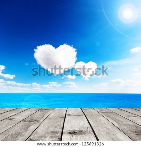 Blue sea under clouds sky with heart shape cloud and wooden pier. Valentine background - stock photo