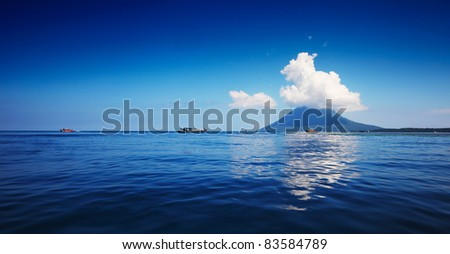 Blue sea with boats and mountain on a horizon. Bunaken marine park. Indonesia