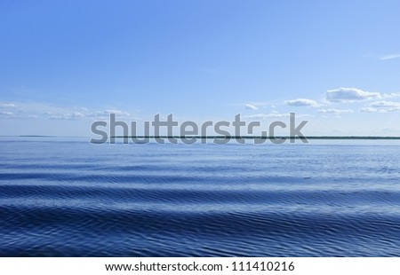Blue sea with waves and blue sky with clouds