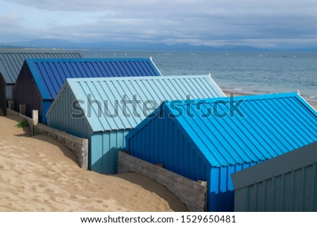Blue seaside huts on the shore.