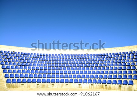 Blue seats and bright sky in an open air stadium