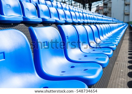 Blue seats on the grandstand of the football stadium.