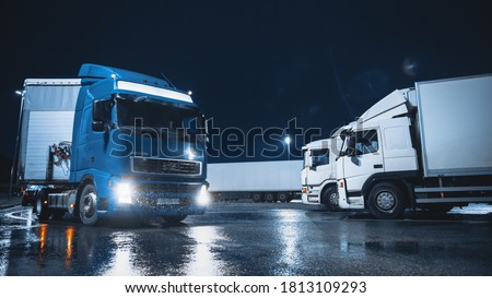 Blue Semi-Truck with Cargo Trailer Drives Off From Overnight Parking Space where Other Trucks are Standing. Long Haul Truck Leaves Parking Lot, Transporting Cargo / Goods Across Continent. Rainy Night Сток-фото ©