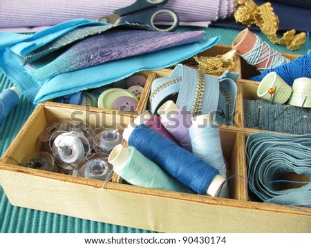 Blue sewing utensils in wooden box