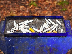 Blue shabby dirty street ashtray with many cigarette butts