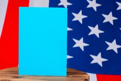 Blue sheet of paper on the background of the American flag. A piece of paper with space for your text on a wooden surface. Mockup on the background of the us flag.