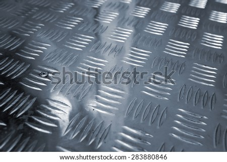 Blue shining metal floor surface with industrial diamond plate relief pattern