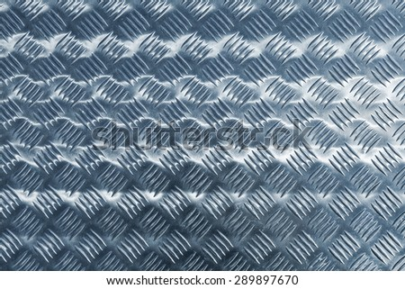 Blue shining metal floor surface with industrial diamond plate relief pattern, blue toned