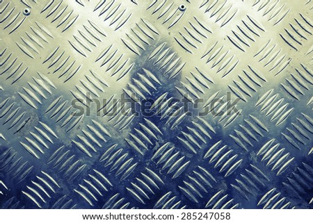 Blue shining metal floor surface with industrial diamond plate relief pattern, vintage tonal correction filter, old style instagram effect
