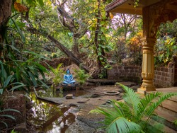 blue Shiva idol in park around temple with tress and small pond